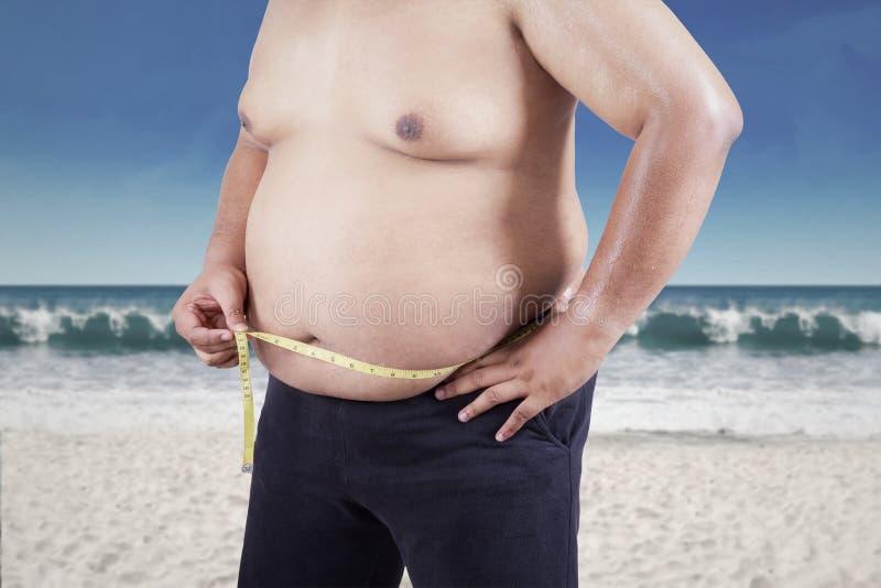 Παχύ άτομο που μετρά το μέγεθος στομαχιών του στοκ εικόνες