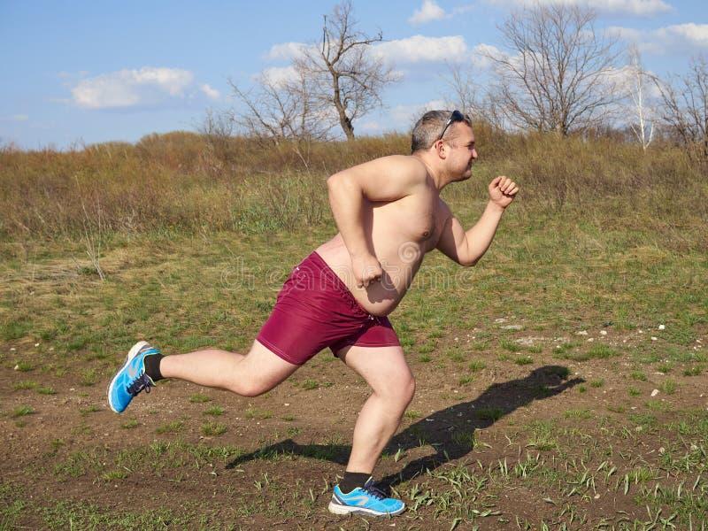 Παχύ άτομο που τρέχει υπαίθρια στη φύση στοκ φωτογραφία