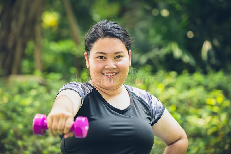 παχύ ευτυχές χαμόγελο κοριτσιών με την αθλητική υπαίθρια άσκηση αλτήρων στοκ φωτογραφία με δικαίωμα ελεύθερης χρήσης