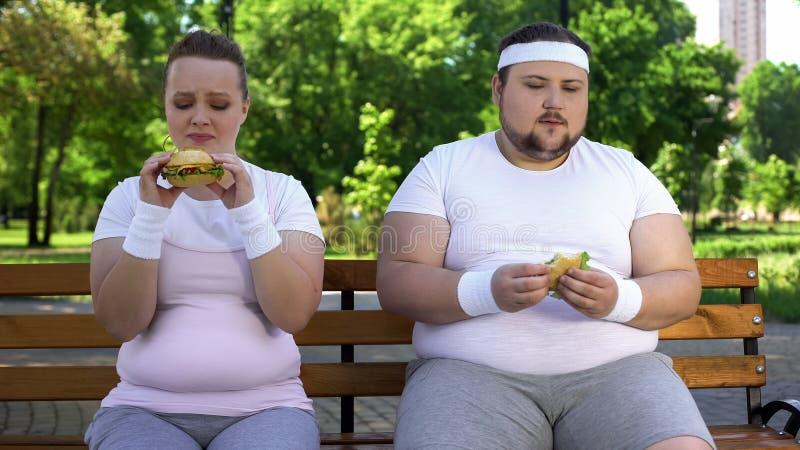 Παχύ νέο ζεύγος που τρώει τα χάμπουργκερ, που εθίζονται στο άχρηστο φαγητό, έλλειψη willpower στοκ φωτογραφία με δικαίωμα ελεύθερης χρήσης