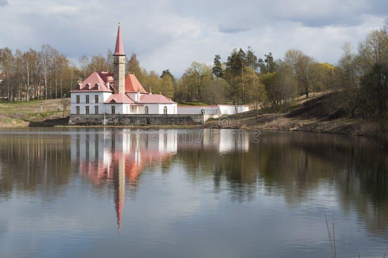 Παλάτι κοινοβίων στην ακτή της λίμνης στη Γκάτσινα, Αγία Πετρούπολη Ρωσία οι θάμνοι θολώνουν πράσινα οριζόντια θερινά δέντρα σκια στοκ εικόνα με δικαίωμα ελεύθερης χρήσης