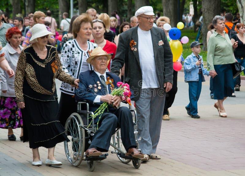 Παλαίμαχος Δεύτερου Παγκόσμιου Πολέμου σε μια αναπηρική καρέκλα και συνοδευόμενος από τους συγγενείς στον εορτασμό ημέρας νίκης σ στοκ εικόνες με δικαίωμα ελεύθερης χρήσης