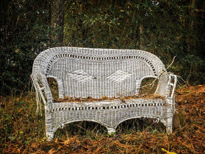 Παλαιά άσπρη ψάθινη έδρα στα ξύλα στοκ εικόνες