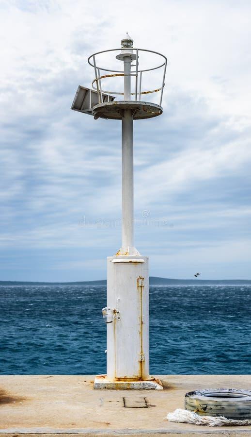 Παλαιά αποβάθρα με ένα αναγνωριστικό σήμα φάρων και μια ήρεμη θάλασσα στοκ εικόνα με δικαίωμα ελεύθερης χρήσης