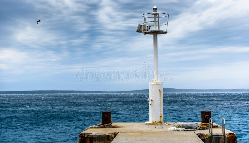 Παλαιά αποβάθρα με ένα αναγνωριστικό σήμα φάρων και μια ήρεμη θάλασσα στοκ εικόνες με δικαίωμα ελεύθερης χρήσης