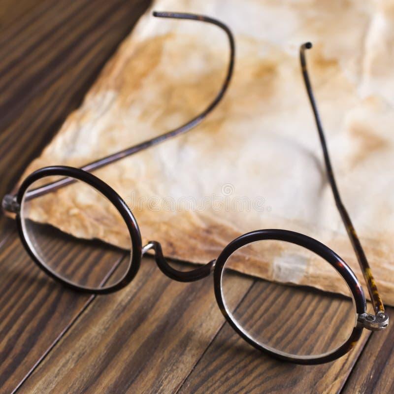 Παλαιά γυαλιά στο εκλεκτής ποιότητας έγγραφο στοκ εικόνες
