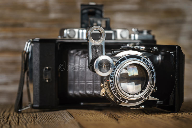 Παλαιά διπλώνοντας κάμερα σε μια κατασκευασμένη αγροτική ξύλινη επιφάνεια στοκ φωτογραφία