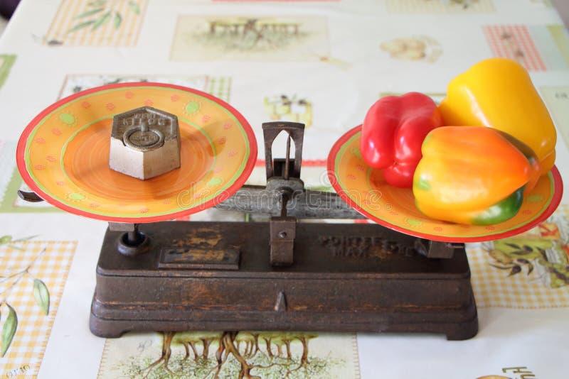 Παλαιά κλίμακα ισορροπίας δύο τηγανιών με τα πιπέρια στοκ φωτογραφία