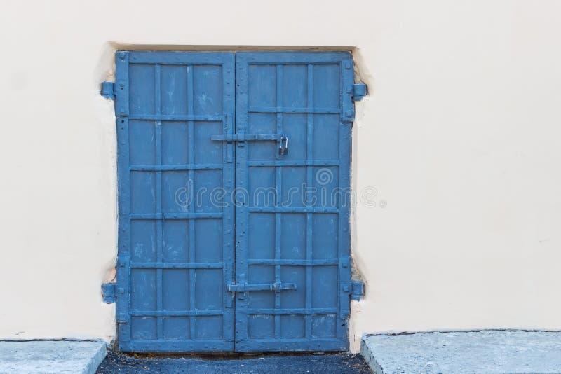 Παλαιά μπλε πόρτα χάλυβα σε ένα υπόβαθρο στοκ εικόνα με δικαίωμα ελεύθερης χρήσης