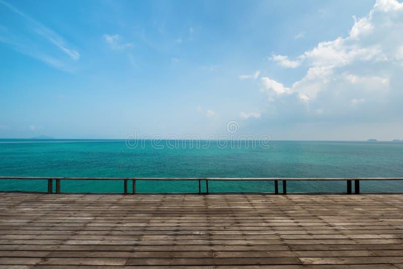 Παλαιά ξύλινη γέφυρα με την ανοικτή θάλασσα στοκ φωτογραφίες