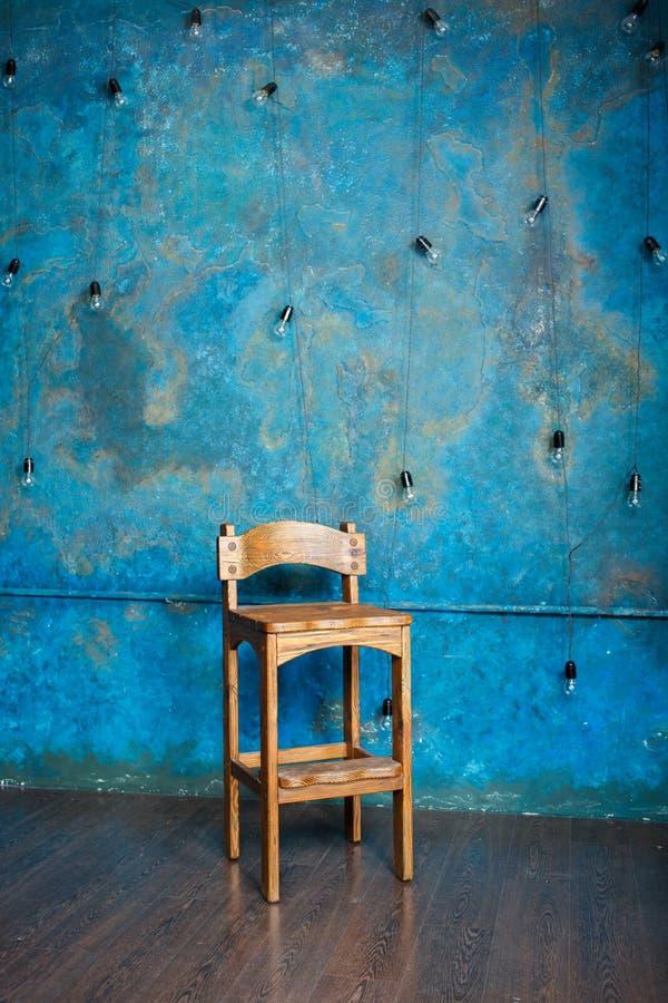Παλαιά ξύλινη καρέκλα στο δωμάτιο grunge με τον μπλε τοίχο στοκ εικόνες με δικαίωμα ελεύθερης χρήσης