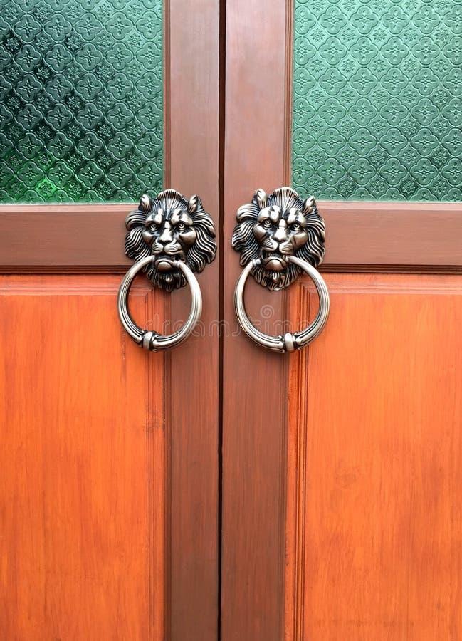 Παλαιά ξύλινη πόρτα που διακοσμείται με ένα κεφάλι λιονταριών ως τα ρόπτρα στοκ εικόνα