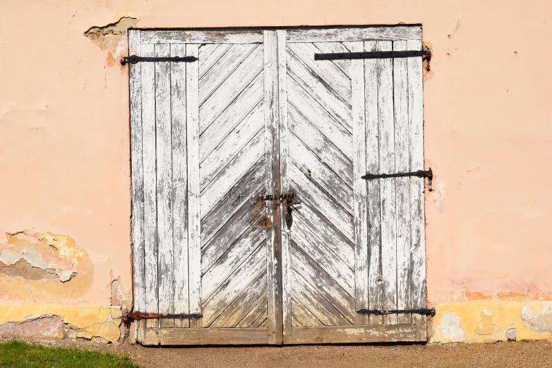Παλαιά ξύλινη πύλη στον μπεζ τοίχο στοκ φωτογραφία με δικαίωμα ελεύθερης χρήσης