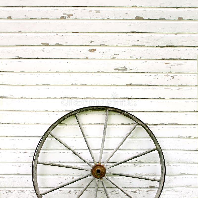 Παλαιά ξύλινη ρόδα βαγονιών εμπορευμάτων στο αγροτικό άσπρο υπόβαθρο στοκ εικόνες