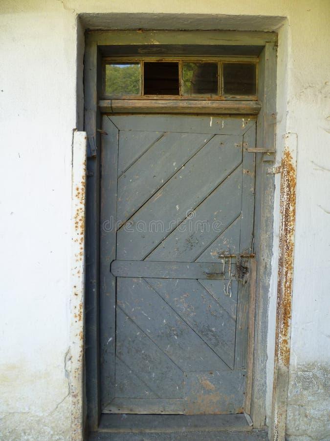 Παλαιά πόρτα από τη σιταποθήκη με το σπασμένο παράθυρο στοκ φωτογραφία