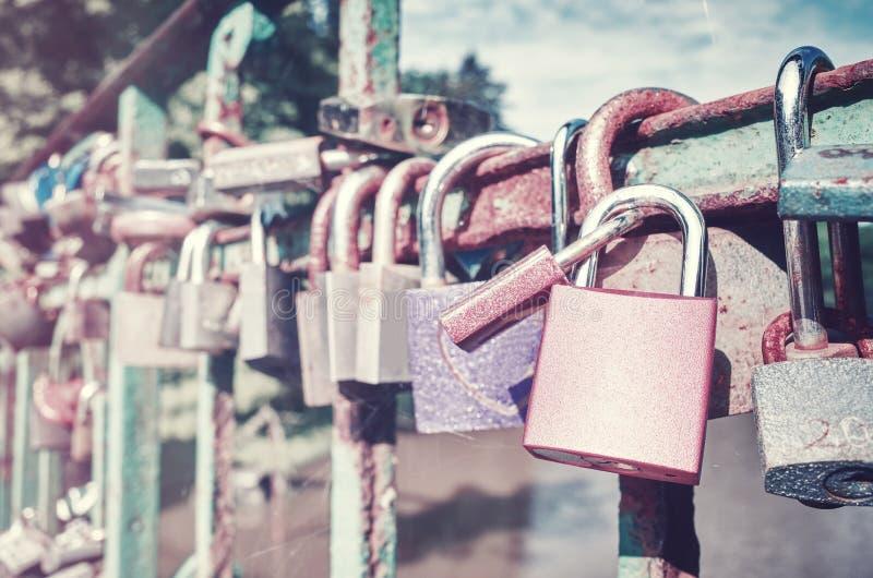 Παλαιά σκουριασμένα λουκέτα αγάπης σε μια γέφυρα στοκ εικόνα