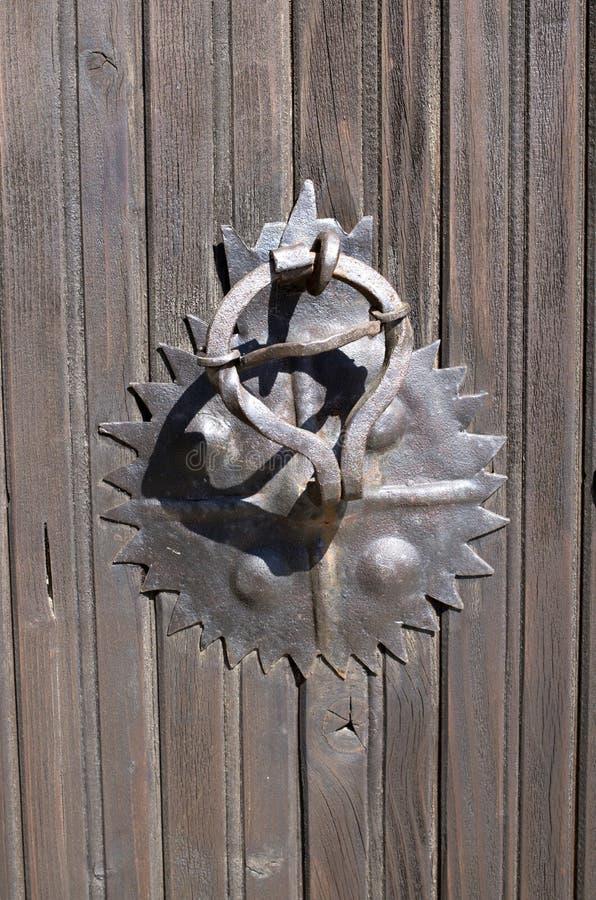 Παλαιά σκουριασμένη στρογγυλή λαβή μετάλλων στην ξύλινη πόρτα στοκ φωτογραφία με δικαίωμα ελεύθερης χρήσης