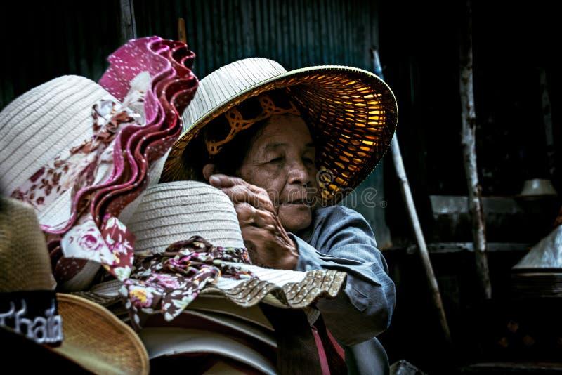 Παλαιά ταϊλανδικά πωλώντας καπέλα γυναικών να επιπλεύσει Damnoen Saduak στην αγορά στοκ εικόνα