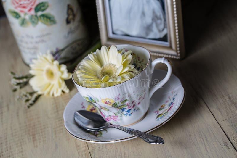 Παλαιά φλυτζάνα τσαγιού με τα κίτρινα λουλούδια μαργαριτών στοκ εικόνες με δικαίωμα ελεύθερης χρήσης