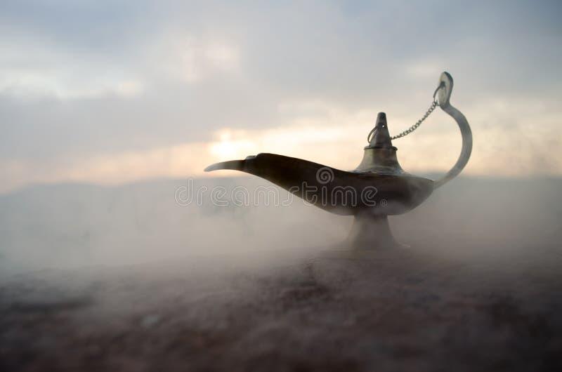 Παλαιά χειρωνακτική ελαιολυχνία ύφους μεγαλοφυίας νυχτών Aladdin αραβική με το μαλακό ελαφρύ άσπρο καπνό Υπόβαθρο βουνών ηλιοβασι στοκ φωτογραφία