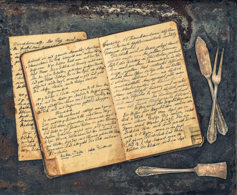 Παλαιές ασημικές και εκλεκτής ποιότητας χειρόγραφο βιβλίο συνταγής στοκ εικόνες