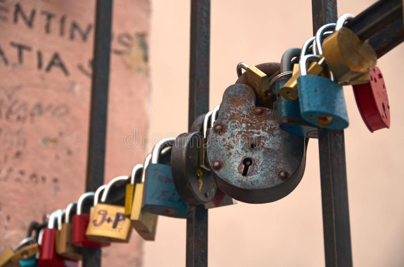 Παλαιές και σκουριασμένες κλειδαριές αγάπης στο δικτυωτό πλέγμα σιδήρου στοκ φωτογραφίες