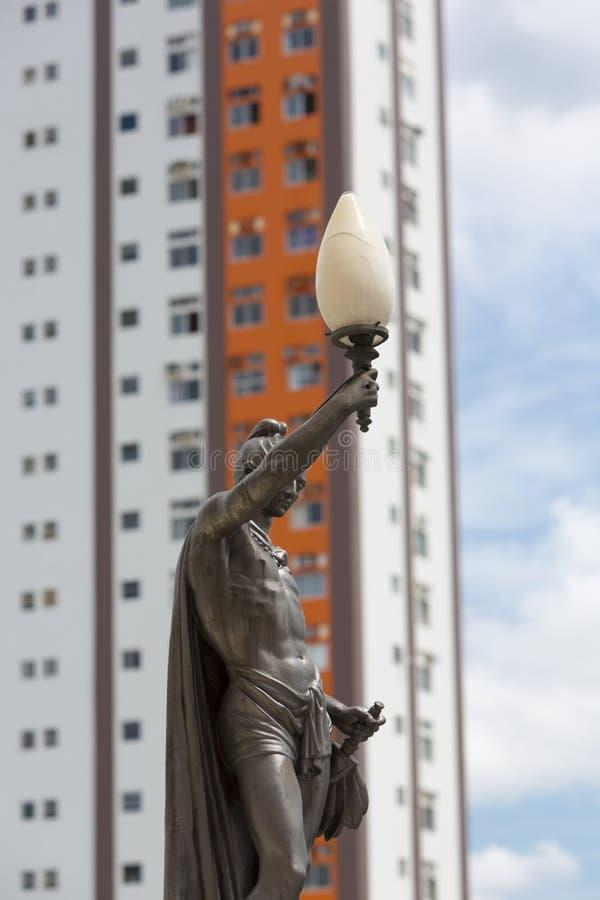 Παλαιοί άγαλμα και φωτεινός σηματοδότης με το σύγχρονο κτήριο, Manaus στοκ εικόνα με δικαίωμα ελεύθερης χρήσης
