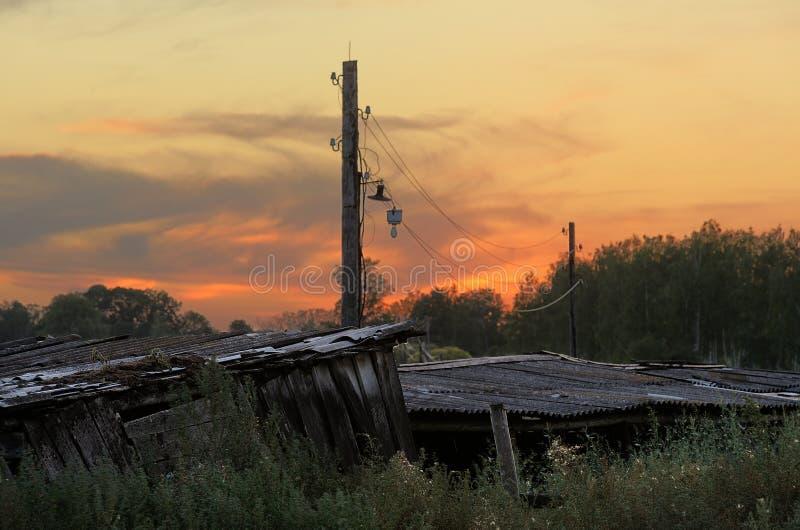 Παλαιοί ξύλινοι υπόστεγο και πόλος στη χώρα στο ηλιοβασίλεμα στοκ εικόνες