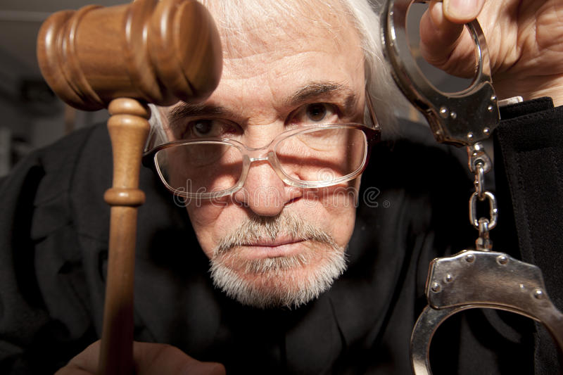Παλαιός αρσενικός δικαστής σε ένα δικαστήριο που χτυπά gavel στοκ φωτογραφία