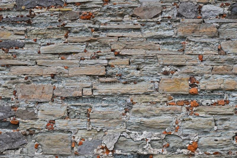 Παλαιός βαλμένος σε στρώσεις πέτρα τοίχος στοκ φωτογραφία με δικαίωμα ελεύθερης χρήσης