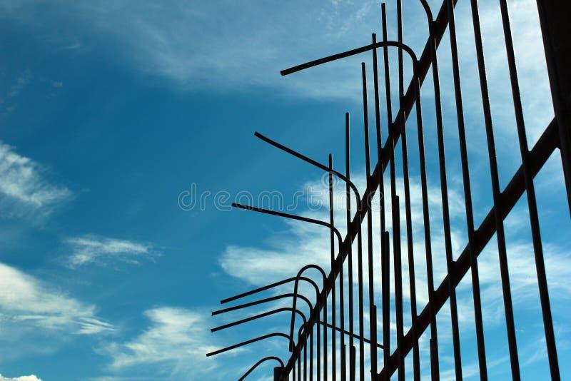 Παλαιός καμμμένος φράκτης μετάλλων στο κλίμα μπλε ουρανού στοκ φωτογραφία με δικαίωμα ελεύθερης χρήσης