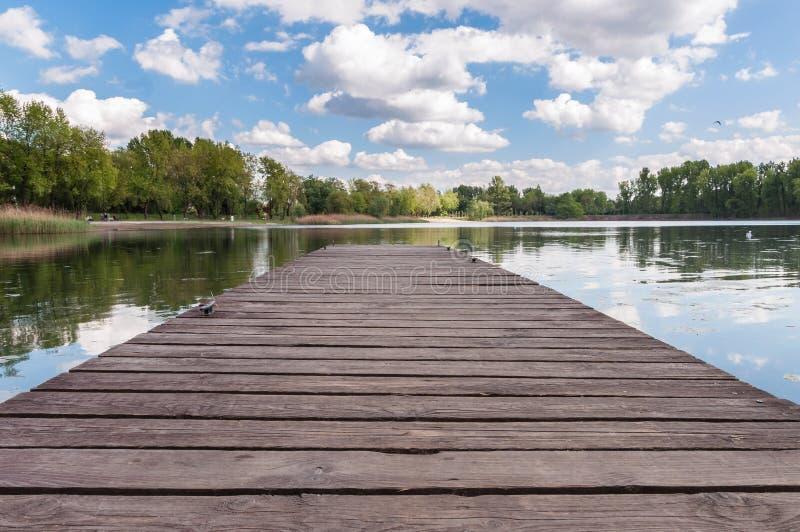 Παλαιός ξύλινος λιμενοβραχίονας σε μια λίμνη στοκ εικόνα