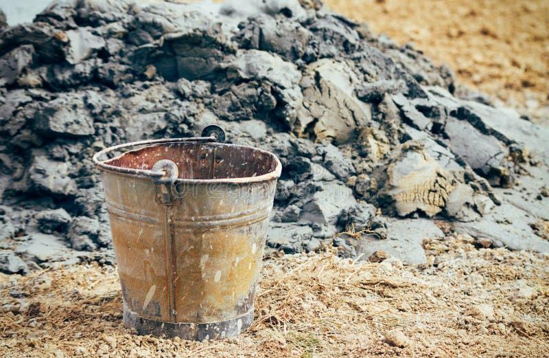 Παλαιός σκουριασμένος κάδος νερού από το σωρό της λάσπης αναδρομικό φίλτρο στοκ εικόνες