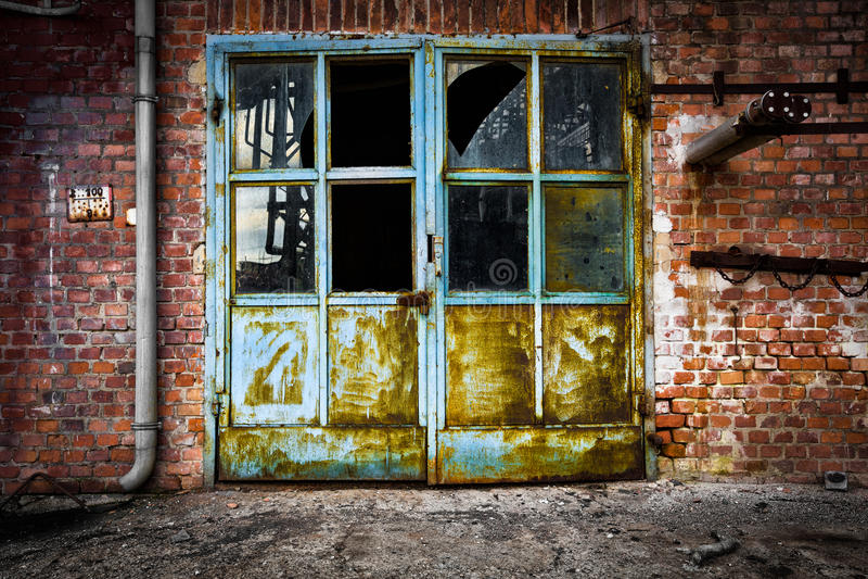 Παλαιός σκουριασμένος τουβλότοιχος γυαλιού πορτών σιδήρου στοκ φωτογραφία με δικαίωμα ελεύθερης χρήσης