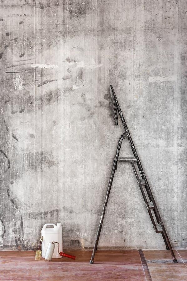 Παλαιός συμπαγής τοίχος στην επισκευή του δωματίου με το βρώμικο πάτωμα, stepladder στοκ φωτογραφία με δικαίωμα ελεύθερης χρήσης