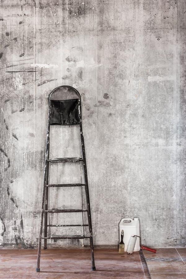 Παλαιός συμπαγής τοίχος στην επισκευή του δωματίου με το βρώμικο πάτωμα και steplad στοκ εικόνες