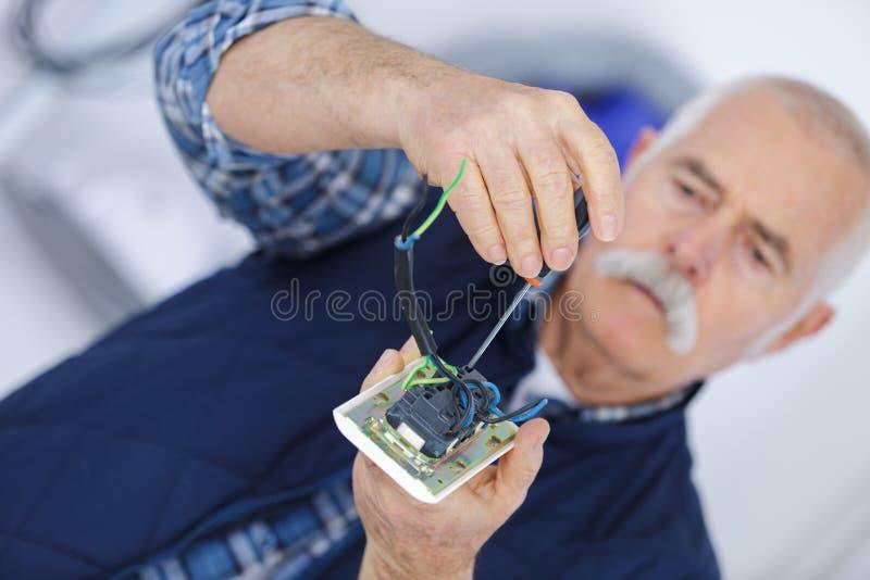 Παλαιότερο αρσενικό που επισκευάζει τους ηλεκτρονικούς εξοπλισμούς στοκ φωτογραφία