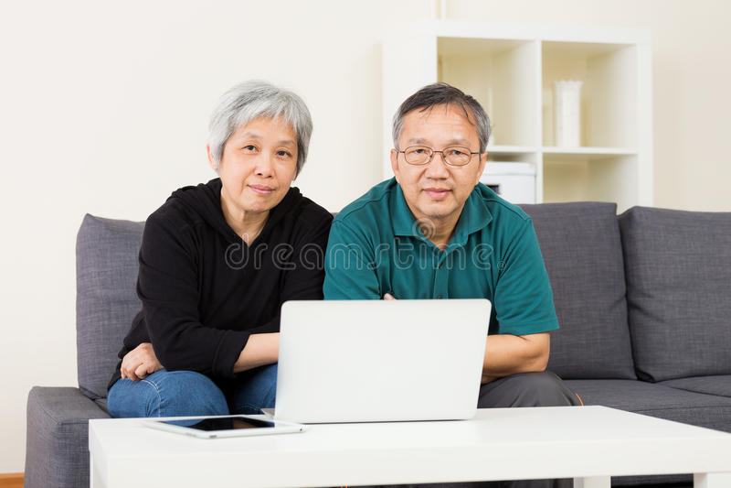 Παλαιότερο ζεύγος που μένει στο σπίτι με το φορητό προσωπικό υπολογιστή στοκ εικόνες