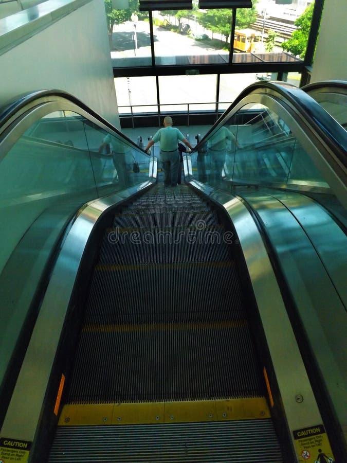 Παλαιότερο ζεύγος που οδηγά μια κυλιόμενη σκάλα στοκ φωτογραφίες