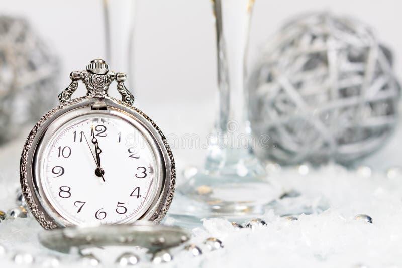 Παλαιό ασημένιο ρολόι κοντά στις διακοσμήσεις μεσάνυχτων και Χριστουγέννων στοκ εικόνες