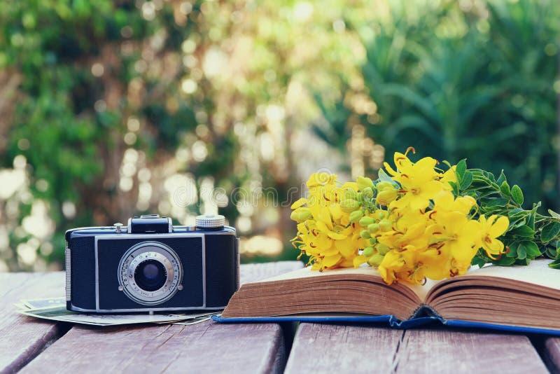 παλαιό βιβλίο, εκλεκτής ποιότητας κάμερα φωτογραφιών δίπλα στα λουλούδια τομέων στοκ φωτογραφία