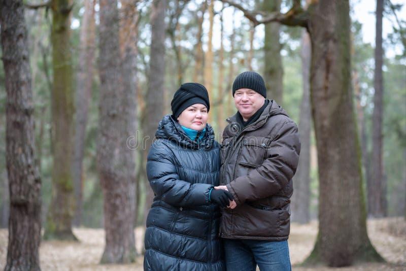 Παλαιό ζεύγος που περπατά στο δάσος περνώντας καλά από κοινού Χαμόγελο και ομιλία στο φθινόπωρο ή την άνοιξη στοκ εικόνες