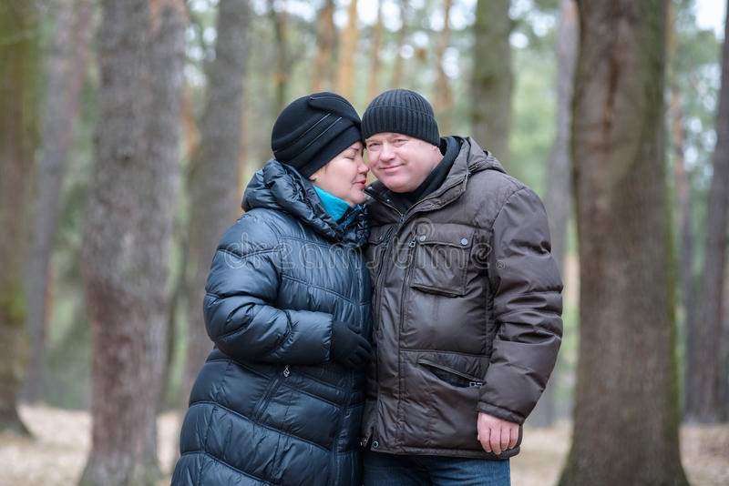 Παλαιό ζεύγος που περπατά στο δάσος περνώντας καλά από κοινού Χαμόγελο και ομιλία στο φθινόπωρο ή την άνοιξη στοκ εικόνα