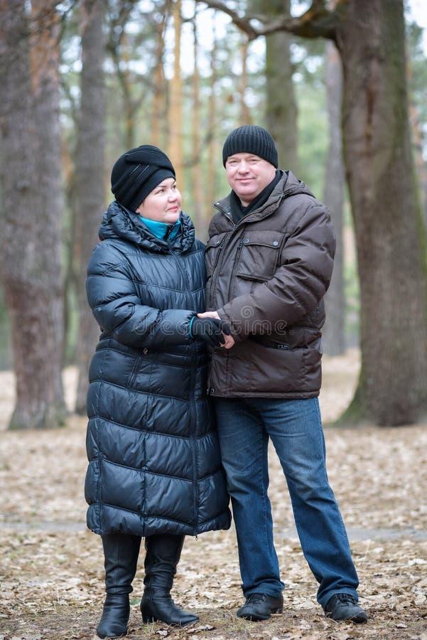 Παλαιό ζεύγος που περπατά στο δάσος περνώντας καλά από κοινού Χαμόγελο και ομιλία στο φθινόπωρο ή την άνοιξη στοκ εικόνα με δικαίωμα ελεύθερης χρήσης