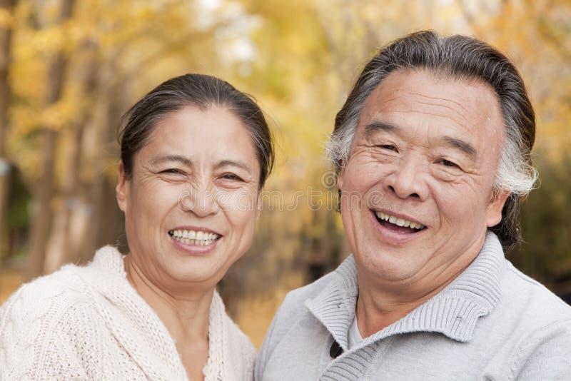 Παλαιό ζεύγος που χαμογελά και που εξετάζει τη κάμερα στο πάρκο στοκ εικόνες με δικαίωμα ελεύθερης χρήσης