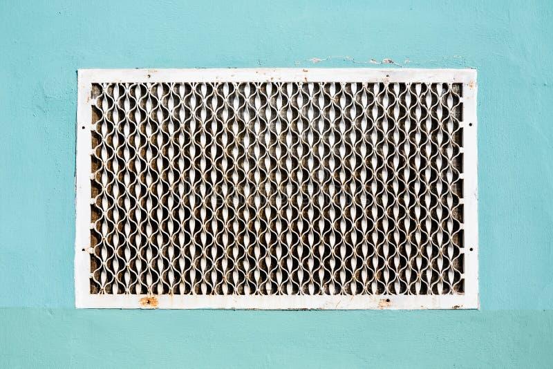Παλαιό διαμορφωμένο μέταλλο πλέγμα εξαερισμού στον επικονιασμένο τοίχο στοκ εικόνα