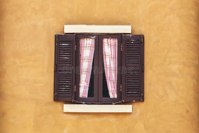 Παλαιό καφετί παράθυρο με την κουρτίνα στον κίτρινο τοίχο στοκ φωτογραφία με δικαίωμα ελεύθερης χρήσης