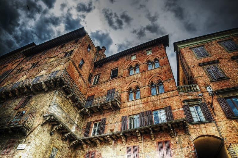 Παλαιό κτήριο στη Σιένα κάτω από έναν δραματικό ουρανό στοκ εικόνες