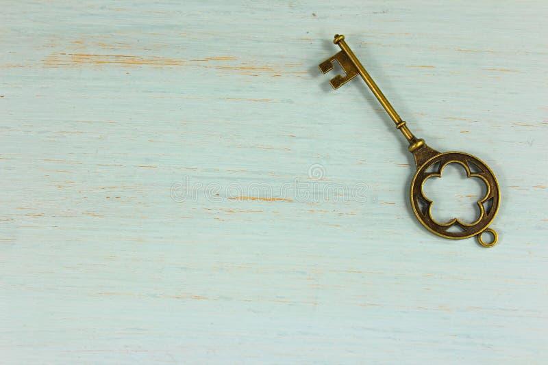 Παλαιό κλειδί ορείχαλκου σε έναν χλωμό - πράσινο στενοχωρημένο ξύλινο υπόβαθρο στοκ φωτογραφίες