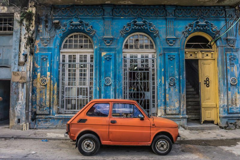 Παλαιό μικρό αυτοκίνητο στο μπροστινό παλαιό μπλε σπίτι στο Λα Αβάνα, Κούβα στοκ φωτογραφία